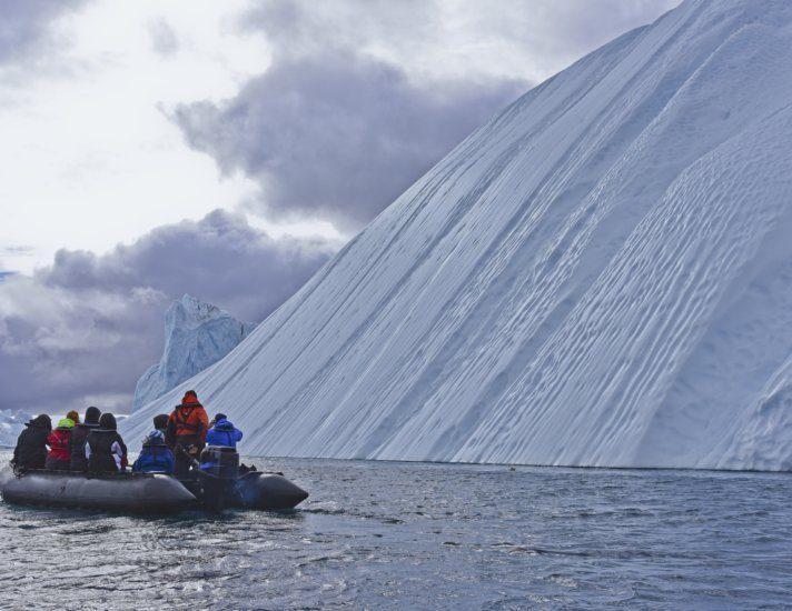 Zodiac tour near enourmous iceberg in the arctic